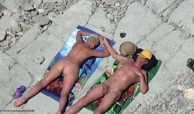 Open-minded couple of lovers are sunbathing totally nude and horny