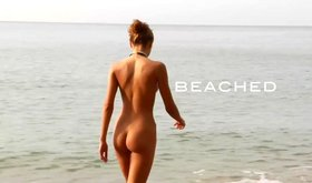 Cunning teen is standing on all fours naked right on the beach