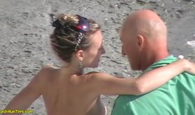 Kinky couple making out on a nudist beach
