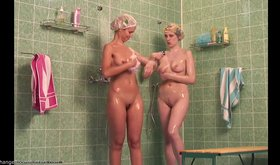 Two naked girlfriends showering next to each other
